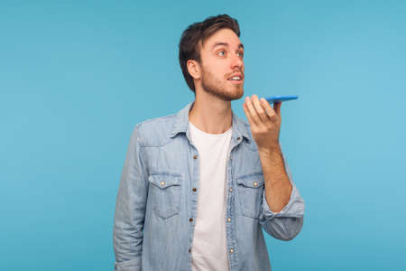 Portrait of positive handsome man in denim shirt talking to cell phone using virtual assistant, digital speaker application. indoor studio shot isolated on blue background