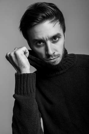 Portrait of handsome man with stylish hairdo wearing warm sweater, pulling sweater collar and looking seductive, flirting at camera, male fashion, vogue concept. black and white, indoor isolated