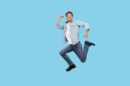 Full length, man in denim outfit flying and jumping in air with inspired ambitious expression, taking big step and hurrying, running to final sale. indoor studio shot isolated on blue background 版權商用圖片