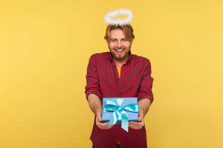 Funny angelic bearded guy with saint halo on head holding gift box, giving present and smiling kind friendly, concept of donation holiday charity. indoor studio shot isolated on yellow background Stock Photo