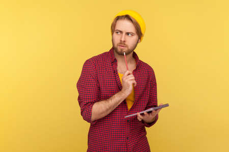 Pensive guy in hipster beanie hat standing thoughtful, pondering idea to write into notebook, taking notes in paper, thinking over business plan, to-do list. studio shot isolated on yellow background