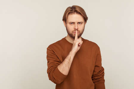 Shut up, be quiet! Portrait of mystery man with beard wearing sweatshirt showing silence gesture with finger on lips, warning to keep secret, confidential information. indoor studio shot isolated