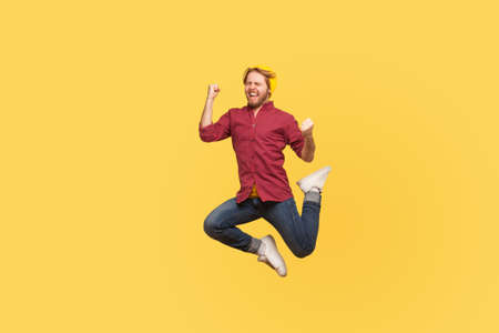 Enthusiastic delighted victorious guy jumping high trampoline, flying in air shouting for joy, crazy about success, triumphal winning. Life people energy concept. full length studio shot isolated Banco de Imagens