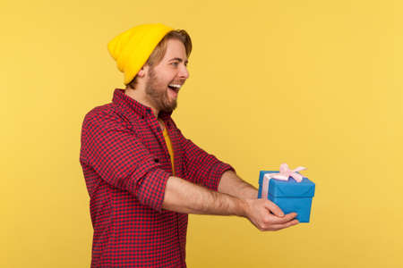 Side view, kind generous hipster guy in beanie hat and checkered shirt offering gift box and smiling friendly amiable, congratulating on birthday anniversary, giving charity. studio shot isolated Stock Photo
