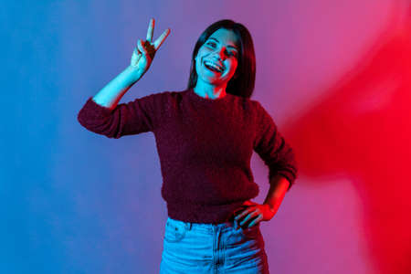 Neon light portrait of carefree happy pretty woman showing victory or peace gesture and smiling broadly, rejoicing lucky winning, feeling optimistic about future success. indoor studio shot isolated Фото со стока