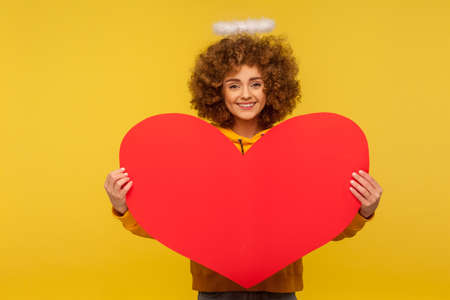 Love you, Happy Valentine's day! Portrait of attractive curly-haired woman with saint nimbus holding big red heart and smiling to camera, demonstrating romantic feelings. indoor studio shot isolated Banco de Imagens