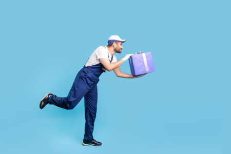 Express service. Side view, professional courier in overalls and protective gloves running to give birthday gift on time, hurrying to deliver present fast. studio shot isolated on blue background