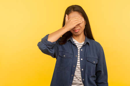 Don't want to look! Portrait of confused upset girl in denim shirt covering eyes, feeling afraid and disgusted to see something shameful, difficult to watch. studio shot isolated on yellow background