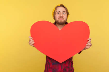 Romantic guy holding big read heart and looking at camera with excitement, demonstrating love affection feelings with huge greeting card on Valentine's Day. studio shot isolated on yellow background