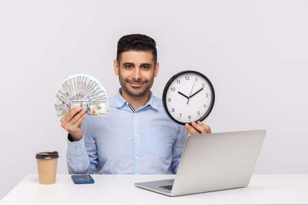Time is money! Happy successful businessman sitting in office workplace, holding big clock and dollar banknotes, looking at camera with friendly smile. indoor studio shot isolated on white background Banco de Imagens
