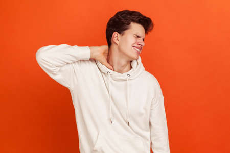 Unhappy worried young man in casual white sweatshirt with hood massaging numb neck, muscle tension, spine injury, osteochondrosis. Indoor studio shot isolated on orange background
