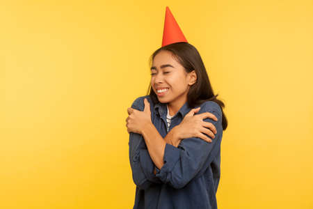 Happy birthday to me! Portrait of girl in denim shirt and with funny party cone on head embracing herself, celebrating successful event alone but happy. studio shot isolated on yellow background Imagens