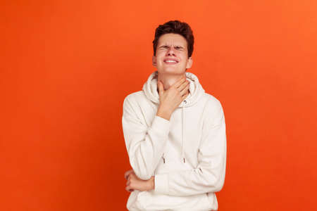 Sad teenager in white hoodie grimacing and closing eyes touching neck, feeling awful pain in throat, pain when swallowing, tonsillitis. Indoor studio shot isolated on orange background