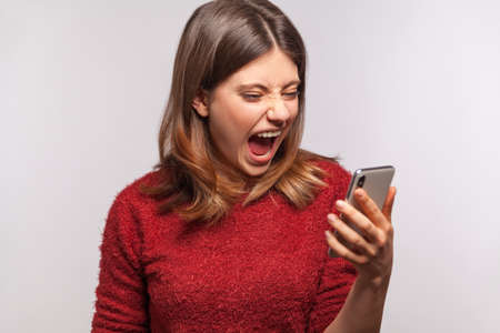 Angry irritated woman keeping mouth open roaring wild, shouting while looking at cell phone screen with crazy furious expression, aggressive mobile user. indoor studio shot isolated on gray background Archivio Fotografico