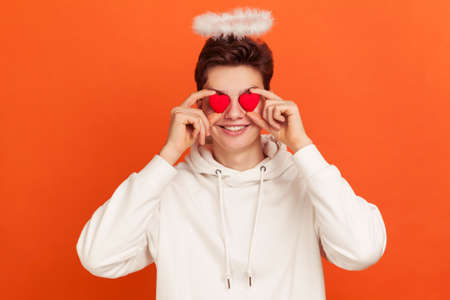 Funny smiling young man in casual hoodie with aureole overhead holding toy hearts near his eyes, pretending to be saint valentine. Indoor studio shot isolated on orange background