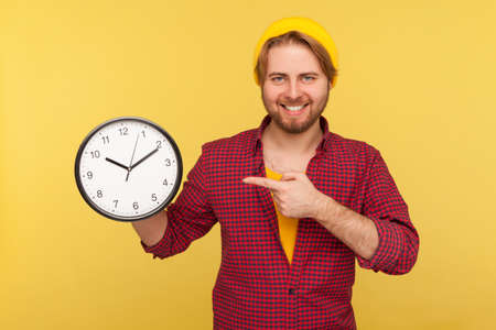 Look at clock, don't rush! Positive hipster guy in checkered shirt pointing big clock and looking at camera with toothy smile, expressing optimism, enough time, not hurry. studio shot isolated