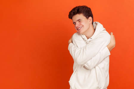 Cute lonely young man in casual style hoodie hugging himself, egoistic teenager proud of his achievements, encouraging. Indoor studio shot isolated on orange background