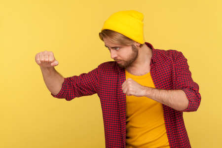 Determined hipster bearded guy in beanie hat, checkered shirt holding clenched fists up ready to boxing, punching with confident expression, fighting spirit. studio shot isolated on yellow, side view