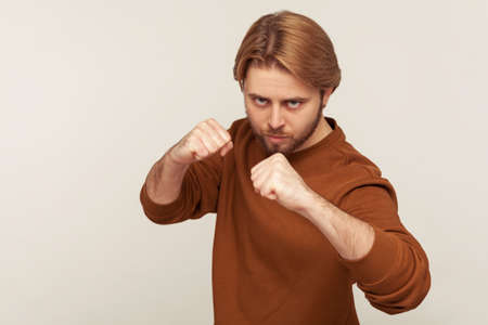 I'll hit you! Portrait of bearded man in sweatshirt standing with raised fists boxing gesture, threatening to punch, ready to struggle, fighting spirit. indoor studio shot isolated on gray background
