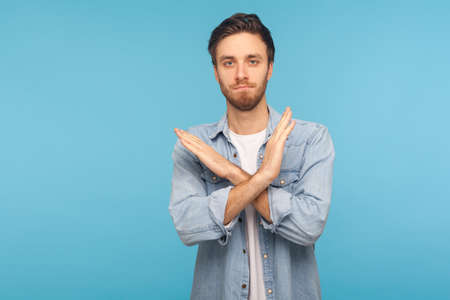 Finish, this is the end. Portrait of serious man in worker denim shirt standing with crossed hands, showing x sign meaning stop, warning of troubles. indoor studio shot isolated on blue background