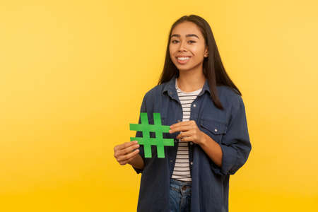 Popular internet idea, viral topic. Portrait of happy girl in denim shirt holding hashtag symbol and smiling to camera, promoting blog, web trends. indoor studio shot isolated on yellow background