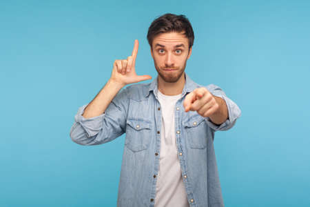 Hey, you failed! Portrait of man in worker denim shirt showing loser gesture and pointing to camera, accusing for mistake, expressing disrespect. indoor studio shot isolated on blue background