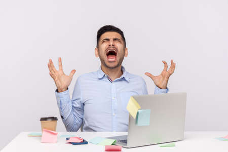 Mad crazy man employee sitting in office workplace with sticky notes all around, shouting furious angry, pissed off deadline and stressful job, screaming wild roar. indoor studio shot isolated Banco de Imagens