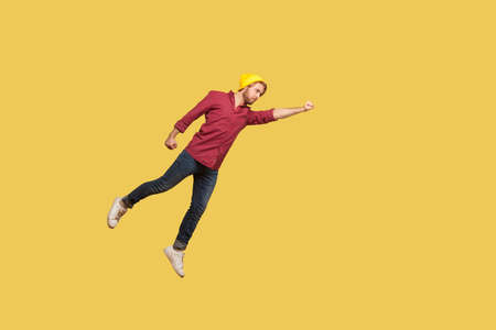 Determined serious ambitious guy flying in air with raised hand, striving forward to victories, feeling super hero power, freedom and confidence to achieve goal. indoor studio shot, yellow background