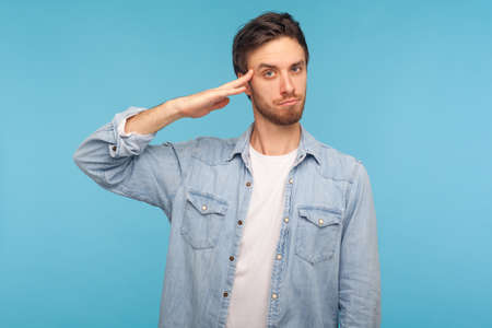 Yes sir! Portrait of responsible patriotic man in worker denim shirt saluting with respect as if soldier waiting order from commander, obeying discipline. studio shot isolated on blue background
