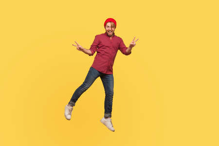 Portrait joyful hipster trendy guy levitating, looking at camera with victory peace gesture, hovering in mid-air, smiling and flying up. full length, indoor studio shot isolated on yellow background 免版税图像