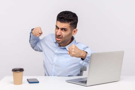 Mad man boss sitting office workplace with laptop, punching to camera and looking furious, boxing threatening to hit, anger management, aggression at work. studio shot isolated on white background