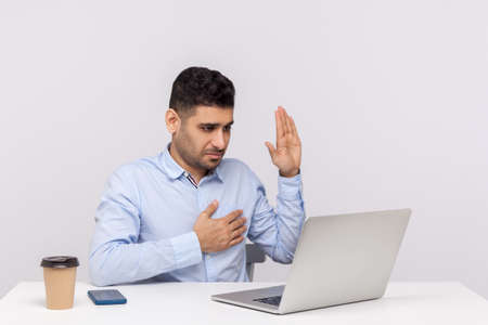 I swear! Honest man employee sitting office workplace, making sincere promise while talking video call on laptop, pledging allegiance, taking vow online. indoor studio shot isolated, white background