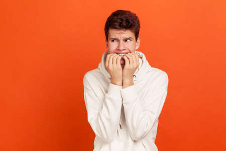 Nervous terrified teenager in white casual style sweatshirt biting his fingers with shocked look, fears and phobias. Indoor studio shot isolated on orange background