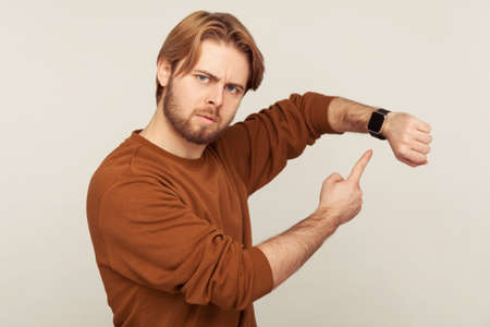 Look at time! Portrait of angry impatient man with beard in sweatshirt pointing wrist watch and looking annoyed displeased, showing clock to hurry up. indoor studio shot isolated on gray background