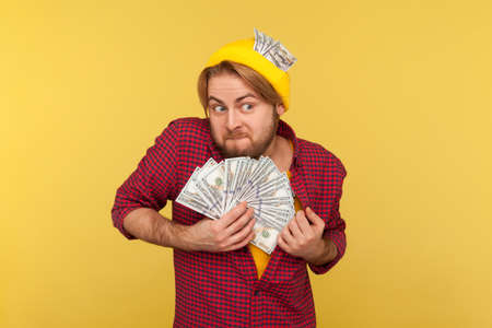 Avaricious hipster guy hiding stolen dollar banknotes in checkered shirt and hat, looking around greedy expression, afraid to lose money, obsessed with finances. indoor studio shot isolated on yellow