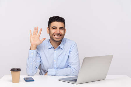 Hi! Friendly happy man employee sitting office workplace with laptop on desk, waving hand gesturing hello, welcoming on reception with toothy smile. indoor studio shot isolated on white background Archivio Fotografico
