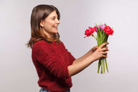 Side view portrait of cheerful happy brunette girl giving flowers bouquet and smiling excitedly. Congratulations on spring holidays, 8 March Women's Day. indoor studio shot isolated on gray background