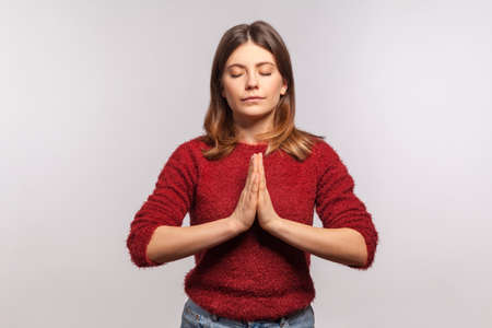 Portrait of calm girl in shaggy sweater concentrating her mind, keeping hands namaste gesture, meditating, yoga exercise breath technique reduce stress. studio shot isolated