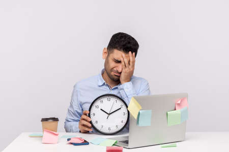 Unhappy sorrowful man employee sitting in office workplace, holding clock and keeping facepalm gesture, expressing regret of missed deadline. studio shot isolated on white background