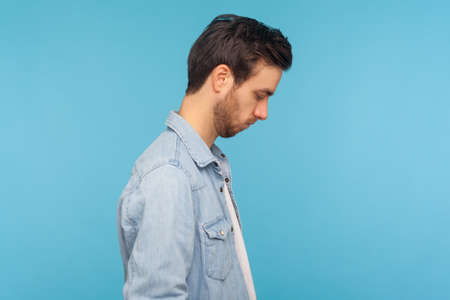 Side view of unhappy man in worker denim shirt looking down, bowing head with sad frustrated expression, feeling depressed, upset about troubles. indoor studio shot isolated on blue background
