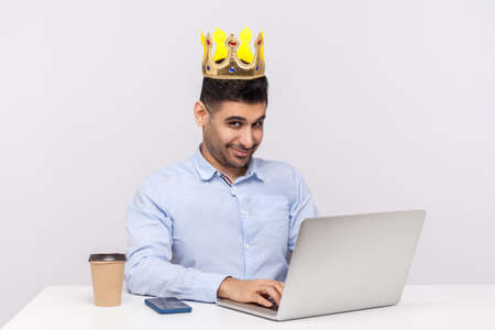 I'm boss! Positive ambitious top manager, office employee with crown on head working on laptop and smiling at camera, feeling proud happy of his position at work. studio shot isolated white background