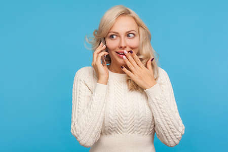 Surprised shocked blond woman in knitted sweater talking phone, discussing friends, amazed with heard news, gossip. Indoor studio shot isolated on blue background