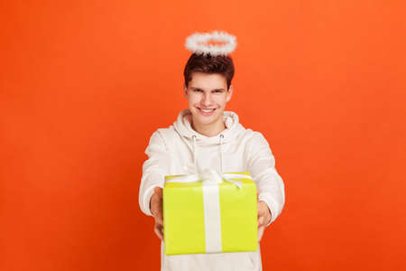 Cheerful young man in casual sweatshirt with kind smile and halo overhead holding gift box, charity organization, religion. Indoor studio shot isolated on orange background