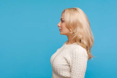 Profile portrait serious assertive blond lady in knitted sweater looking far away, elegant unsmiling woman. Indoor studio shot isolated on blue background