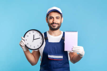 Professional punctual service of house maintenance. Portrait of happy handyman in uniform and gloves holding clock, empty paper for reminder notes, to-do list. studio shot isolated on blue background