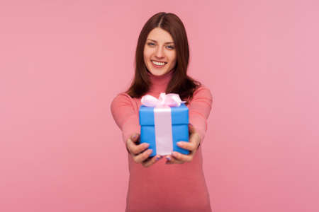 Friendly positive brunette woman holding blue gift box with toothy smile on face, congratulation, holidays. Indoor studio shot isolated on pink background Stock Photo