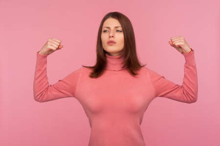 Self confident powerful woman with brown hair raising hands up showing arm muscles demonstrating her strength and freedom. Indoor studio shot isolated on pink background Stock fotó