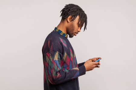 Profile portrait of african man with dreadlocks concentrated looking at smartphone display, absorbed with virtual life, internet connection. Indoor studio shot isolated on gray background Stock fotó