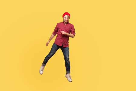 Portrait happy joyful hipster trendy guy levitating, looking at camera with toothy smile, hovering in mid-air, doing step, walking in space isolated. full length, indoor studio shot, yellow background