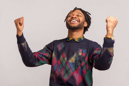 Hurray! Extremely satisfied happy african man with dreadlocks rising hands up with toothy smile on face, pleased, amazed with victory, success. Indoor studio shot isolated on gray background
